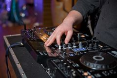 As mãos dos homens pressionam os botões no telecontrole do DJ, ele fazem a música As mãos do DJ no misturador da música em um par foto de stock royalty free