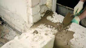 As mãos dos homens puseram o almofariz do cimento sobre os blocos do silicato vídeos de arquivo