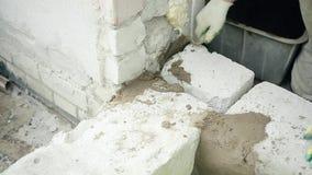 As mãos dos homens puseram o almofariz do cimento sobre os blocos do silicato filme