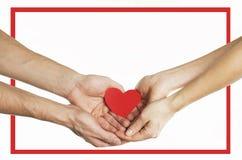 As mãos dos povos guardam um coração vermelho em um quadro vermelho Conceito do relacionamento do dia de Valentim No fundo isolad foto de stock