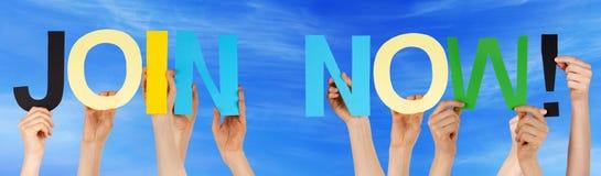As mãos dos povos que guardam a palavra reta colorida juntam-se agora ao céu azul foto de stock royalty free