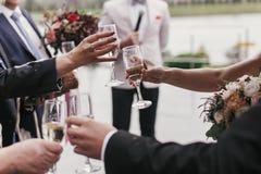 As mãos dos povos que guardam vidros do champanhe e que brindam em wed imagens de stock royalty free