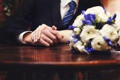 As mãos dos recém-casados com alianças de casamento e o ramalhete do ` s da noiva na tabela Fotografia de Stock