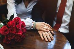 As mãos dos recém-casados com alianças de casamento e o ramalhete do ` s da noiva na tabela Fotos de Stock Royalty Free