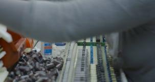 As mãos dos trabalhadores montam manualmente as peças eletrônicas vídeos de arquivo