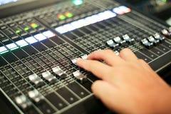 As mãos empurram um console de mistura audio profissional com faders e a foto de stock