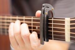 As mãos estão ajustando o capo para ajustar o som do guit fotografia de stock