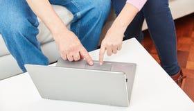 As mãos estão datilografando no teclado de um portátil fotos de stock