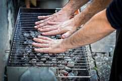 As mãos estão testando o calor do assado no BBQ dos carvões amassados do carvão vegetal foto de stock royalty free