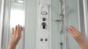 As mãos fêmeas abrem portas deslizantes da cabine do chuveiro Cabine do chuveiro Deslizando o mecanismo de uma cabine do chuveiro imagens de stock royalty free
