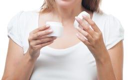 As mãos fêmeas abrem um pacote do close up de creme Fotografia de Stock Royalty Free