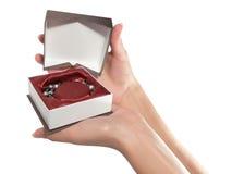 As mãos fêmeas abrem um presente Foto de Stock Royalty Free