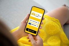 As mãos fêmeas amarelam o telefone da terra arrendada do vestido com o táxi da chamada do app imagens de stock