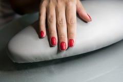 As mãos fêmeas bonitas com os pregos vermelhos na beleza pregam o salão de beleza Pregos e tratamento de mãos fêmeas bonitos imagem de stock