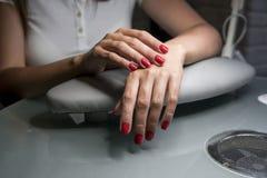 As mãos fêmeas bonitas com os pregos vermelhos na beleza pregam o salão de beleza Pregos e tratamento de mãos fêmeas bonitos fotografia de stock royalty free