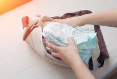 As mãos fêmeas colocam tecidos do bebê em um saco, fim-UPS, tecido imagem de stock royalty free