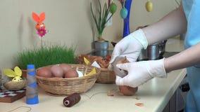 As mãos fêmeas com luvas puseram o shell da cebola e o ovo branco na peúga video estoque