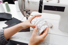As mãos fêmeas com rolos do tamanho etiquetam para a roupa Fotos de Stock Royalty Free