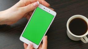 As mãos fêmeas com tratamento de mãos francês bonito tomam um smartphone branco com a tela verde perto da xícara de café branca u vídeos de arquivo