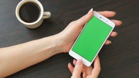 As mãos fêmeas com tratamento de mãos francês bonito tomam um smartphone branco com a tela verde perto da xícara de café branca u filme