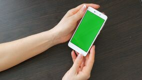 As mãos fêmeas com tratamento de mãos francês bonito tomam um smartphone branco com tela verde Usando Smartphone, guardando video estoque
