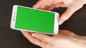 As mãos fêmeas com tratamento de mãos francês bonito tomam um smartphone branco com tela verde Usando Smartphone, guardando vídeos de arquivo