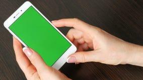 As mãos fêmeas com tratamento de mãos francês bonito tomam um smartphone branco com tela verde Usando Smartphone, guardando filme