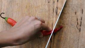 As mãos fêmeas cortaram a pimenta de pimentão vermelho picante na placa de desbastamento Vista superior Vegetariano e alimento ve filme