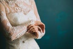As mãos fêmeas da noiva prendem botões na luva em um close-up branco do vestido do vintage do casamento do laço bonito, preparati imagem de stock