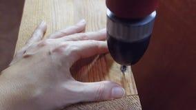 As mãos fêmeas desenrolam o parafuso com uma broca O conceito dos limites de papéis tradicionais do gênero video estoque