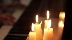 As mãos fêmeas do close-up que jogam o piano em uma obscuridade em umas velas iluminam-se video estoque