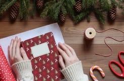 As mãos fêmeas em uma camiseta branca embalam o livro de Natal em uma tabela de madeira Foto de Stock