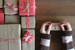 As mãos fêmeas em uma camiseta mantêm um presente em uma superfície de madeira Fotografia de Stock