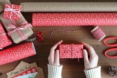As mãos fêmeas embalam um presente do Natal em uma tabela de madeira Imagem de Stock
