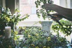 As mãos fêmeas entregam flores de corte para o ramalhete do verão com flores selvagens em uma tabela na sala de visitas moderna fotografia de stock