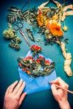 As mãos fêmeas escrevem com o lápis no azul aberto envolvem com flores Florista com flores do outono e equipamento da decoração e Imagem de Stock Royalty Free
