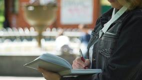 As mãos fêmeas escrevem para baixo ideias em um caderno vídeos de arquivo