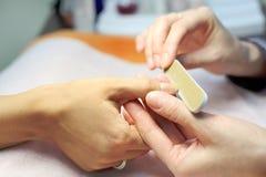 As mãos fêmeas fazem o manicure por nailfile para a mulher Imagens de Stock