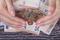 As m?os f?meas fecham-se fora de uma pilha de euro- c?dulas e moedas em uma tabela de madeira preta fotos de stock royalty free