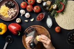 As mãos fêmeas friccionaram o queijo raspado na pizza, ingredientes para cozinhar a pizza na tabela preta, vista superior Fotos de Stock Royalty Free