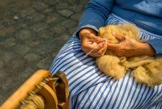 As mãos fêmeas gerenciem lãs cruas dos carneiros em uma roda de giro Fotos de Stock Royalty Free