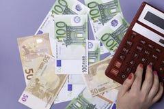 As mãos fêmeas guardam contas do EURO e uma calculadora em um fundo azul - o conceito da contabilidade Vista superior fotografia de stock