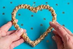 As mãos fêmeas guardam o coração decorativo dourado Zombaria acima Conceito do dia de Valentim imagem de stock royalty free
