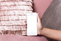 As mãos fêmeas guardam o telefone celular com zombaria branca da tela acima em um fundo interior cor-de-rosa foto de stock