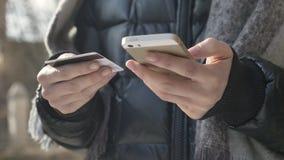 As mãos fêmeas guardam um grande cartão preto do smartphone e de crédito, operação bancária em linha, compra, fps em linha da loj vídeos de arquivo