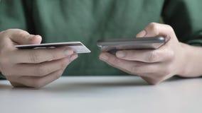 As mãos fêmeas guardam um grande cartão preto do smartphone e de crédito, operação bancária em linha, fps da compra 60 video estoque
