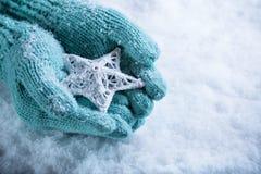 As mãos fêmeas na cerceta clara fizeram malha mitenes com a estrela branca entrelaçada em um fundo branco da neve Conceito do inv Imagem de Stock