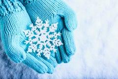 As mãos fêmeas na cerceta clara fizeram malha mitenes com o floco de neve maravilhoso efervescente em um fundo branco da neve Con fotografia de stock royalty free