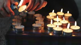 As mãos fêmeas novas iluminam velas em uma caixa de presente vídeos de arquivo