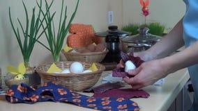 As mãos fêmeas puseram o ovo branco no material de seda Pintura dos ovos da páscoa filme